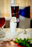 Wedding wine glass. Closeup wuth red drink and roses royalty free stock image