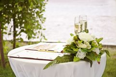 Wedding wineglass. Wineglass,flowers and register book on the table Royalty Free Stock Images
