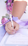 The wedding, the witness puts his signature on the document. The wedding, the witness puts his signature on a document, selective focus Royalty Free Stock Image