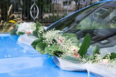 Wedding wreath of fresh roses and silk ribbon on bumper of blue car royalty free stock photo