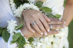 Weddings hands. Hands with wedding bands over flowers Royalty Free Stock Photo