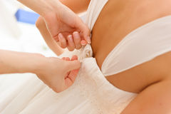 Weddings preparation, zipping-up white dress. stock photos