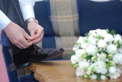 Weddings preparations. A young man strings laces putting a leg on a table which a white nosegay lies on Stock Images