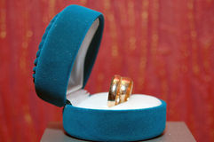 Weddings rings in a blue box. A red background Royalty Free Stock Photo