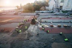 Wederopbouw en verbetering van stadsvierkant Bouwvakkers die steentegels plaatsen royalty-vrije stock afbeelding