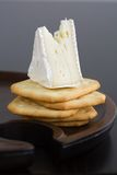 Wedge of Brie cheese on butter crackers Royalty Free Stock Images
