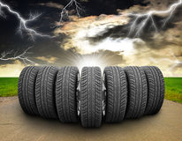 Wedge of car wheels. Road, roadsides, grass field. Wedge of new car wheels. Road, roadsides and grass field. Stormy sky with lightning in background Stock Images