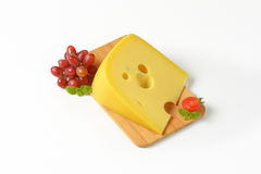 Wedge of cheese with red grapes Stock Photo