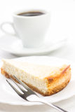 Wedge of cheesecake with dessert fork and cup of coffee Royalty Free Stock Images