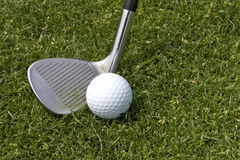 Wedge and Golf ball. A wedge set up to hit golf ball Royalty Free Stock Photography