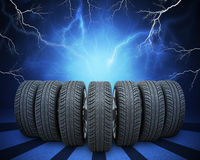 Wedge of new car wheels. Abstract background with. Wedge of new car wheels. Abstract blue background with lightning and stripes at bottom Stock Photos
