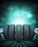 Wedge of new car wheels. Green background is night Royalty Free Stock Photography