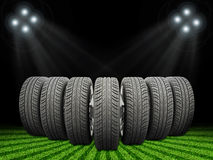 Wedge of new car wheels. Green grass, stripes at Stock Photography