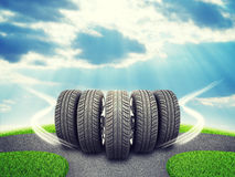 Wedge of new car wheels on road fork  and green Royalty Free Stock Photography