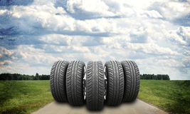 Wedge of new car wheels on road stretches into the Stock Photos