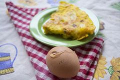 Wedge of omelette togheter at fresh eggs. Wedge potato omelette and fresh eggs with shell Stock Photos