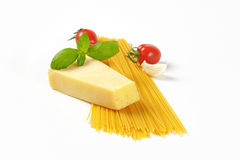 Wedge of parmesan cheese and spaghetti Stock Images