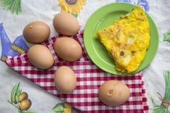 Wedge of omelette togheter at fresh eggs. Wedge potato omelette and fresh eggs with shell Stock Images