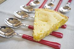 Wedge of ricotta tart on a composition of colored spoons Stock Image