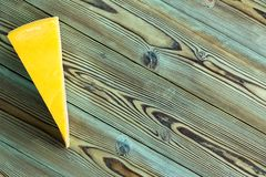 Wedge of traditional Dutch Maasdam cheese. With its yellow rind placed to the side on a rustic pine picnic table with copy space royalty free stock images