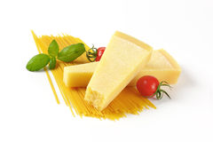 Wedges of parmesan cheese and spaghetti Stock Photography