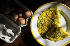 Flat lay of frittata in constrast of light. Wedges of vegetarian frittata with near fresh eggs stock image