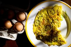 Flat lay of frittata in constrast of light. Wedges of vegetarian frittata with near fresh eggs stock photography
