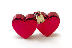 Wedlocked, two hearts locked, on white. Two red hearts connected with padlock, on white background Stock Image