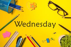 Wednesday. Office supplies or student outfit on yellow table. Business creative consept, top view.  royalty free stock image