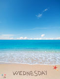 Wednesday on a tropical beach under clouds. Wednesday written on a tropical beach under clouds stock images