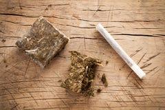 Weed marijuana hashish roll wood background Stock Images