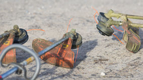 Weed Trimmers. Four well used weed trimmers laying in a semicircle on a sandy road. Dirty orange trimmer guards and heads covered with grass clippings. Trimmer Stock Image