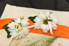 Weeding rings pinned on white daisies. White cushion and orange ribbon decoration for wedding rings Royalty Free Stock Photography