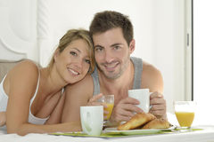 Week-end breakfast. Cheerful young couple having breakfast in bed Stock Photos