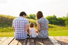 Week-end, enfants et concept de condition parentale - famille s'asseyant sur la surface en bois et regardant la belle vue d'été Photos libres de droits