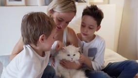 Week-end heureux - jeune maman avec les enfants heureux jouant chez le chat blanc de lit et de gingembre se trouvant sur le lit d banque de vidéos