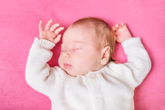 2 week old baby with closed eyes wearing knitted white clothes. Lying on pink plaid. Sweet little baby sleeping on pink sofa. Security and childcare concept royalty free stock images