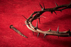 Week of passion. Jesus Christ crown of thorns and a nail on red background Royalty Free Stock Photography