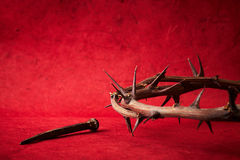 Week of passion. Jesus Christ crown of thorns and a nail on red background Stock Photography