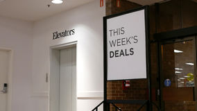 This week`s deals billboard beside elevators Stock Photo