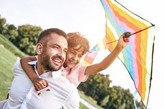 Weekend activities. Father carrying son on his back holding kite. Walking on field in nature looking aside smiling happy stock image