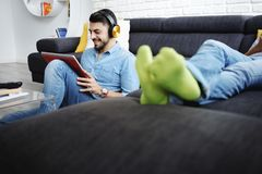 Couple Lying On Sofa With Tablet PC and Earphones Stock Photos