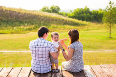 Weekend, children and parenthood concept - Family sitting on the wooden surface and looking at the beautiful summer view Royalty Free Stock Photos
