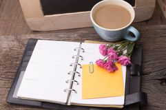 Weekend concept. Pink rose, mug with coffee, diary and stcky not Royalty Free Stock Image