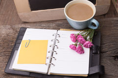 Weekend concept. Pink rose, mug with coffee, diary and stcky not Royalty Free Stock Images