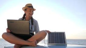 Weekend da nuova tecnologia, da seduta femminile sul tetto dell'automobile con il taccuino e dalla batteria sul cielo del fondo i video d archivio