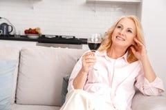 Weekend die op middelbare leeftijd van de vrouwenvrije tijd het thuis omhoog ontspannen kijken stock fotografie
