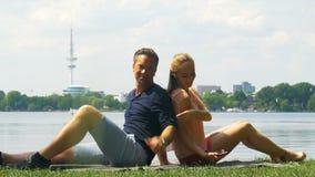 Weekend - een paar die op de rivieroever ontspannen en aan muziek op hoofdtelefoons luisteren stock video