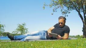 Weekend en la ciudad - un hombre se relaja en la hierba en el parque y lee un libro almacen de metraje de vídeo