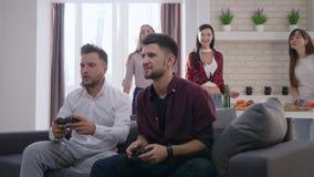 Weekend, facet sztuki gra wideo na konsolach siedzi na kanapie na backgrounf firma przyjaciele cieszy się spoczynkowy salowego we zbiory wideo